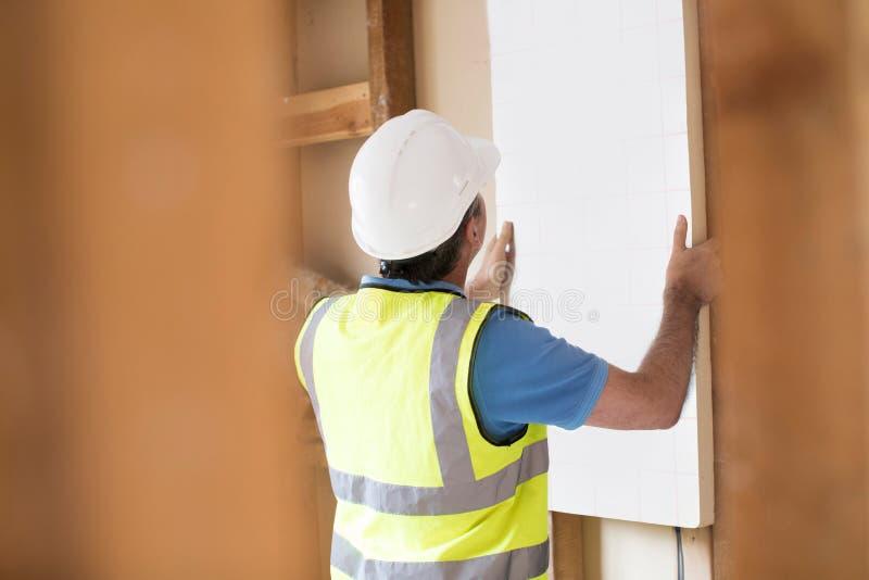 Byggmästare Fitting Insulation Boards in i taket av det nya hemmet fotografering för bildbyråer