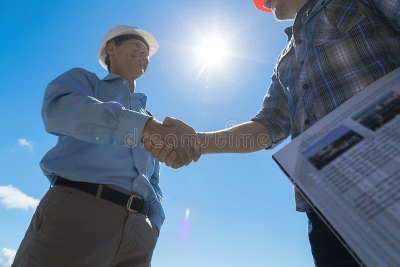 Byggmästare handskakning, arkitekt And Contractor Agreement under möte som diskuterar det ritningBuiding planet på konstruktion arkivbild