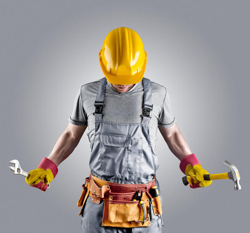 Byggmästare i en hjälm med en hammare och en skiftnyckel royaltyfri fotografi