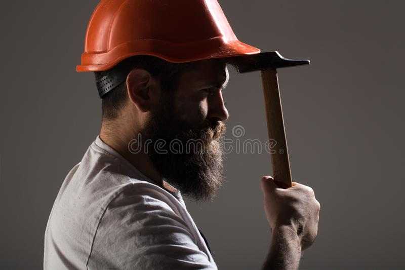 Byggmästare i hjälmen, hammare, faktotum, byggmästare i hardhat Skäggig manarbetare med skägget, byggnadshjälm, hård hatt arkivfoto