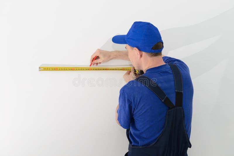 Byggmästare i likformig av att mäta avstånd på väggen med en måttband fotografering för bildbyråer