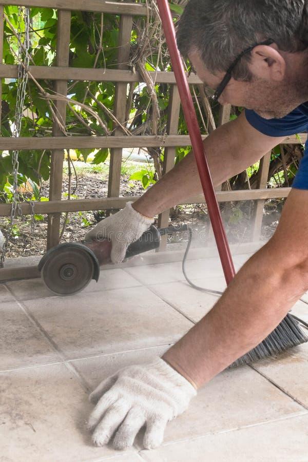 Byggmästare i likformign som klipper tegelplattor med den elektriska skäraren på verandan royaltyfri fotografi