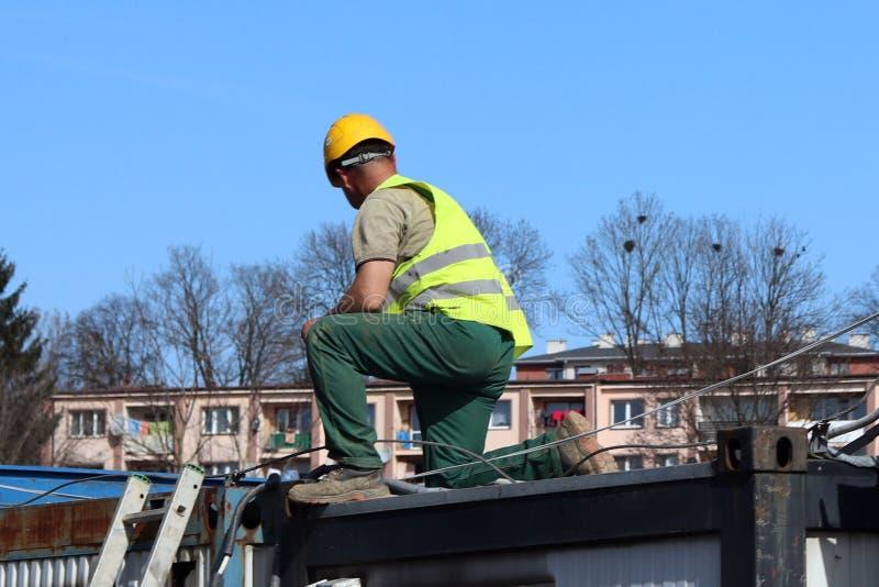 Byggmästare i overaller på konstruktionsplatsen Reparationer på höjd ny byggnadskonstruktion Yrket av en byggmästare Hea royaltyfri foto
