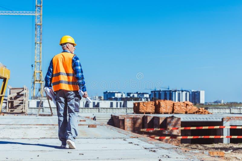 Byggmästare i reflekterande väst och hardhat som går över en konstruktionsplats med rullar av plan royaltyfria bilder