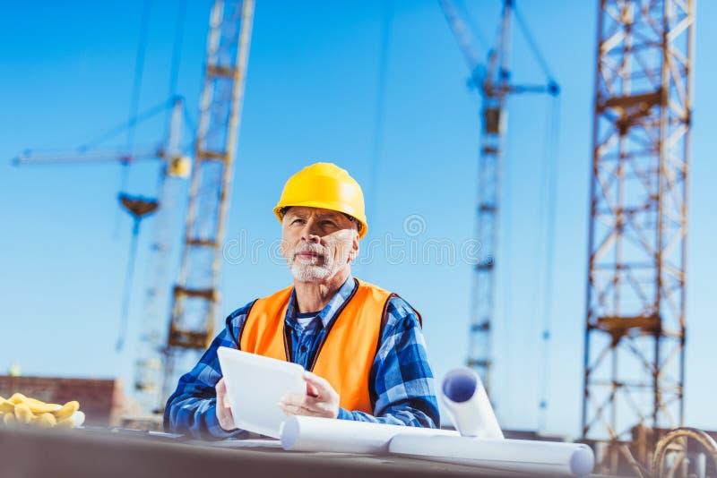 Byggmästare i reflekterande väst- och hardhatanseende på det konstruktionsplatsen och innehavet royaltyfri fotografi