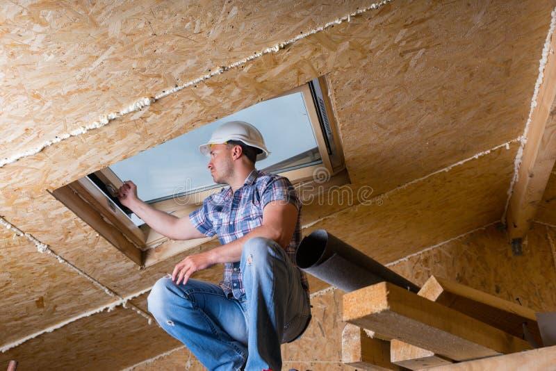 Byggmästare Inspecting Skylight i oavslutat hus arkivfoton
