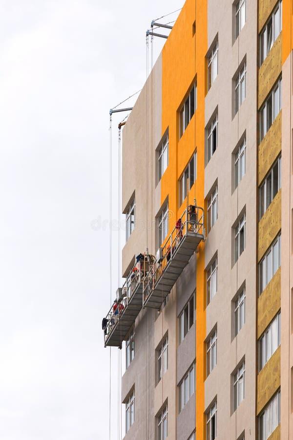 Byggmästare målar fasaden av en bostads- byggnad för höghus royaltyfria foton