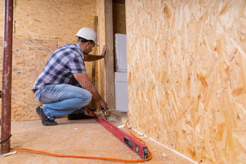 Byggmästare Measuring Door Frame i oavslutat hem arkivbilder