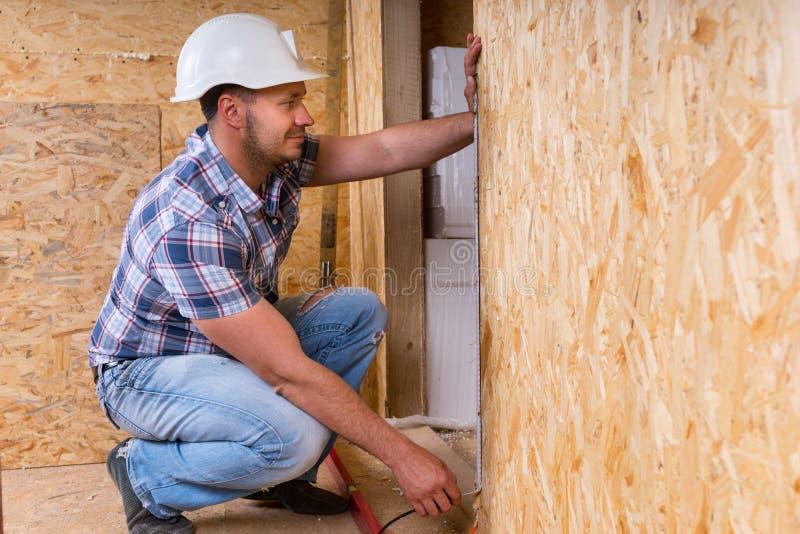 Byggmästare Measuring Door Frame i oavslutat hem fotografering för bildbyråer