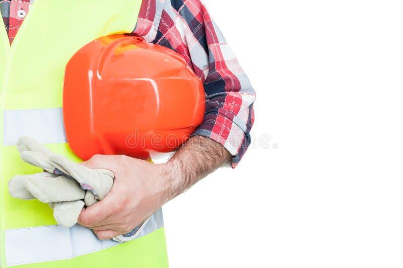 Byggmästare med den orange hjälmen och funktionsdugliga handskar arkivfoto