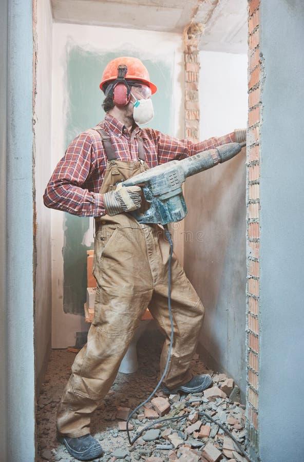 Byggmästare med rivninghammaren som bryter innerväggen arkivbild