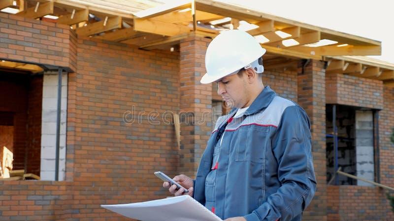 Byggmästare med utkast genom att använda telefonen på plats arkivbild