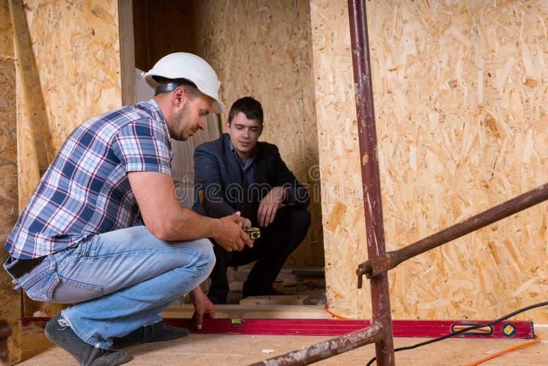 Byggmästare och arkitekt Inspecting Building Doorway arkivfoto