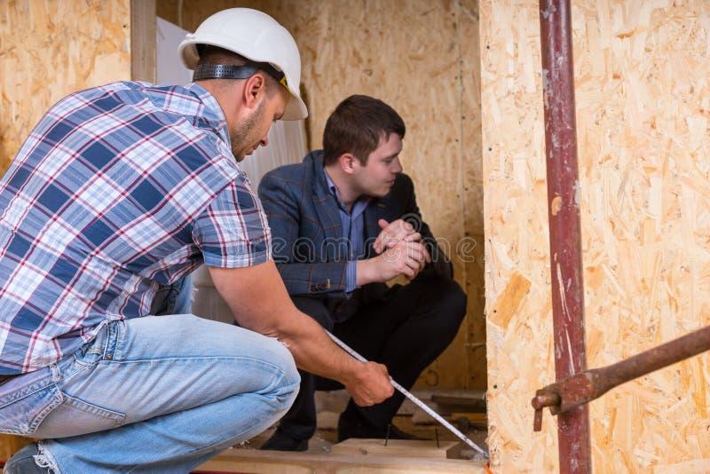 Byggmästare och arkitekt Inspecting Building Doorway arkivbilder
