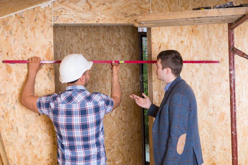 Byggmästare och arkitekt Inspecting Door Frame arkivfoto