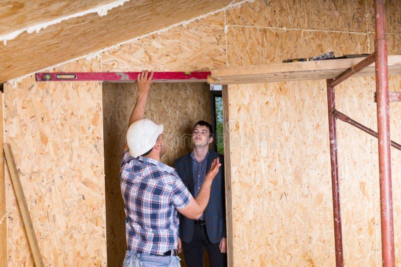 Byggmästare och arkitekt Inspecting Door Frame arkivbild