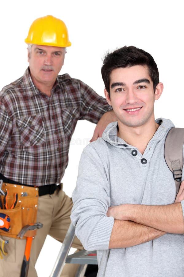 Byggmästare och en högskolestudent royaltyfria foton