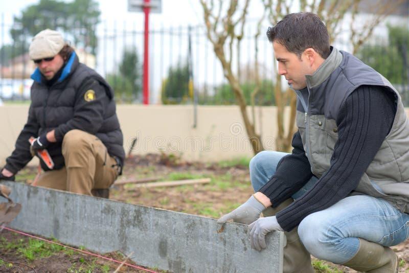 Byggmästare på arbete i trädgård arkivfoto