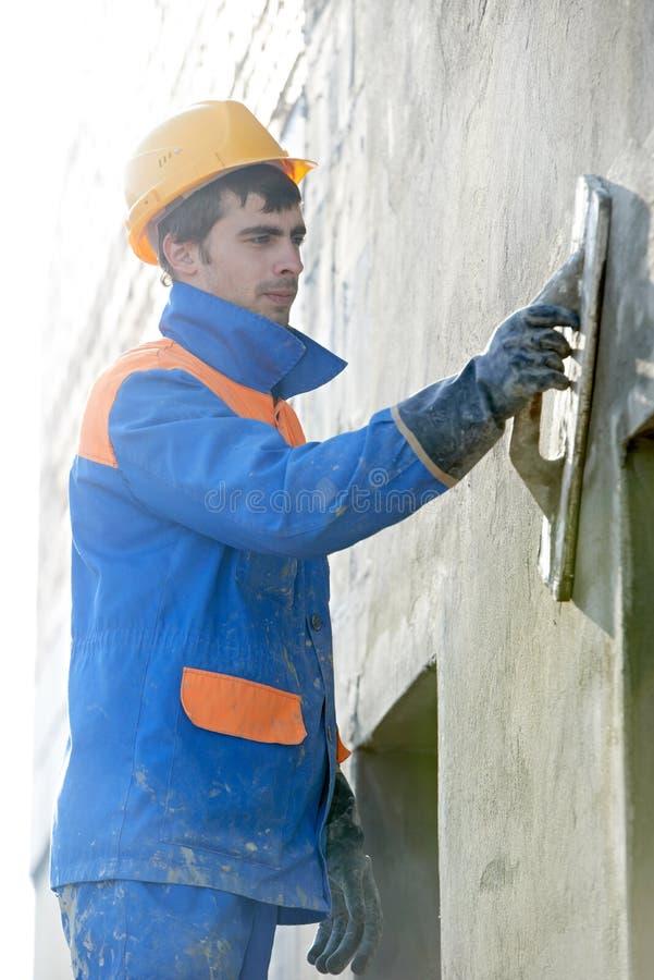 Byggmästare på fasaden som rappar arbete med spackelflötet fotografering för bildbyråer