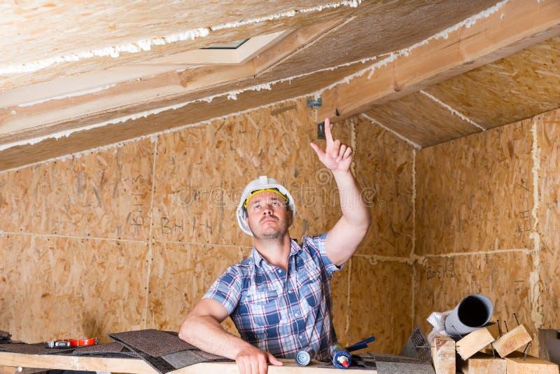 Byggmästare Pointing Up på taket i oavslutat hem arkivbild