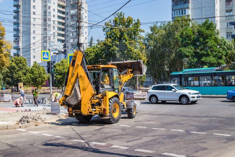 Byggmästare reparerar trottoaren med industriell utrustning arkivfoto