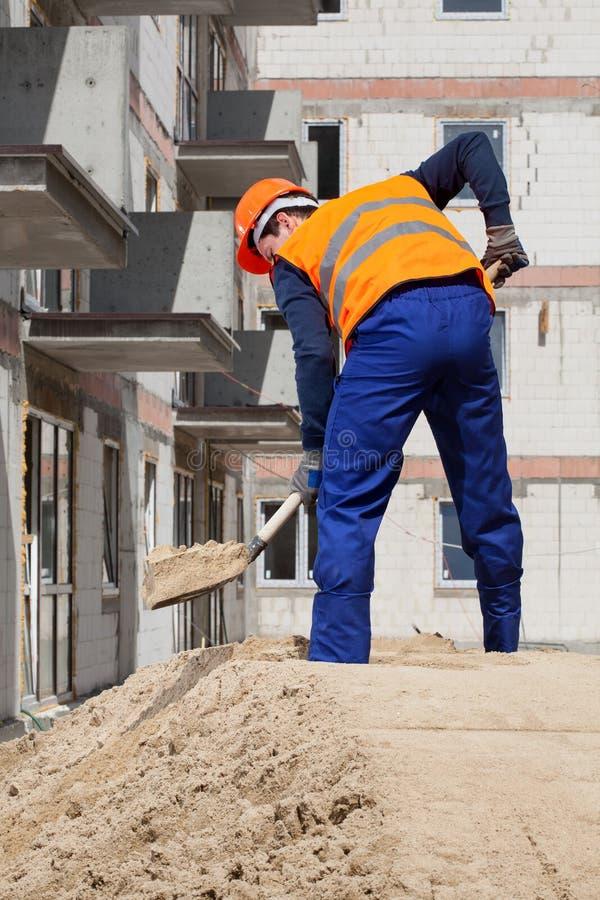 Byggmästare som arbetar genom att använda skyffeln royaltyfri foto