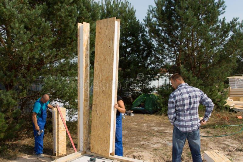 Byggmästare som arrangera i rak linje isolerade väggpaneler royaltyfria foton