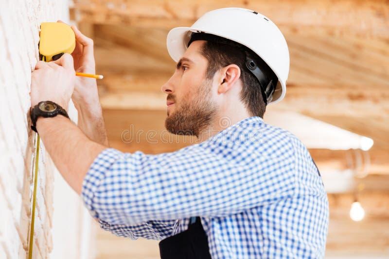 Byggmästare som gör mått i ett nytt hus arkivfoton