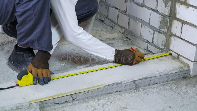 Byggmästare som gör mått med att mäta bandet och blyertspennan på konstruktionsplatsen royaltyfri fotografi