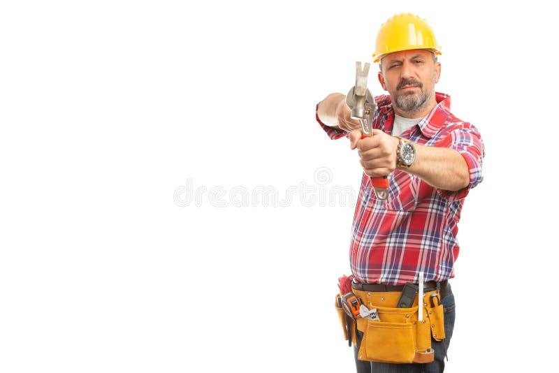 Byggmästare som gör syftegest genom att använda hammaren och skiftnyckeln arkivbild