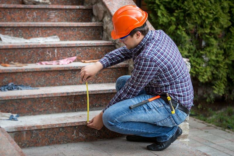 Byggmästare som kontrollerar trappahöjd, genom att mäta bandet royaltyfri bild