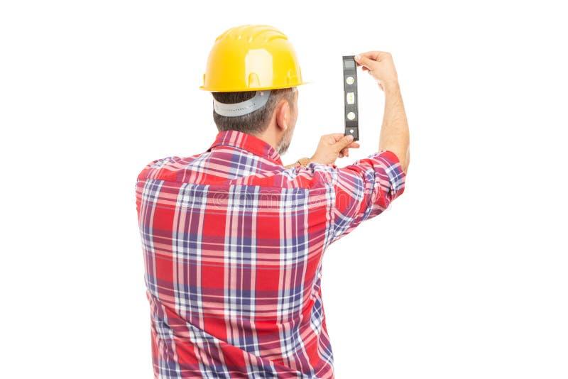 Byggmästare som kontrollerar yttersida med bubblanivån royaltyfri foto