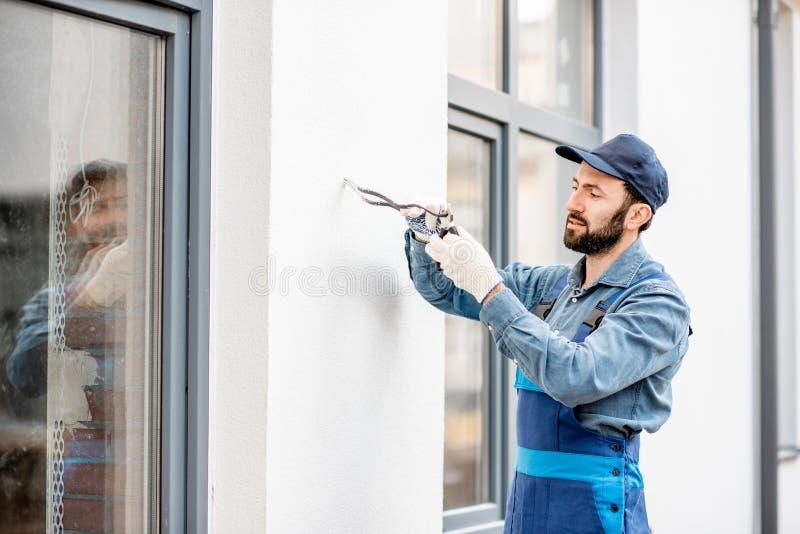 Byggmästare som monterar ledningsnät för utomhus- belysning arkivfoton