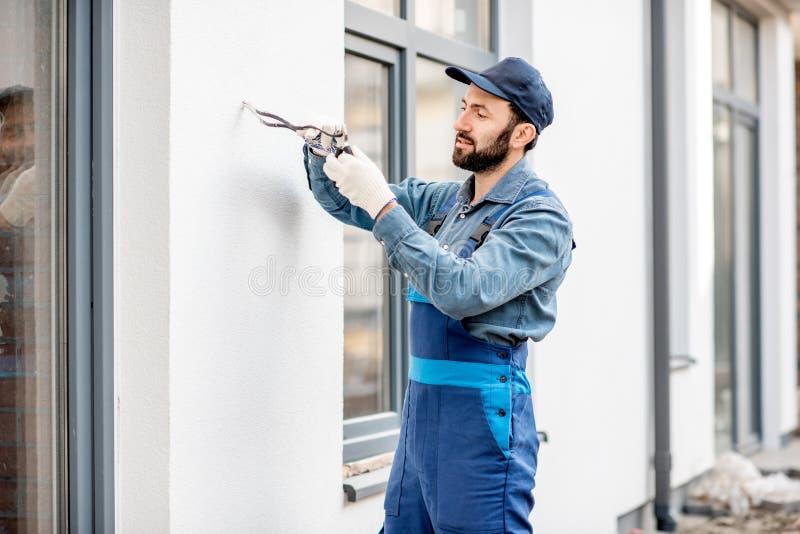 Byggmästare som monterar ledningsnät för utomhus- belysning royaltyfri foto