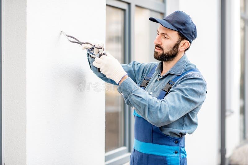 Byggmästare som monterar ledningsnät för utomhus- belysning royaltyfri bild