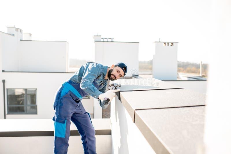 Byggmästare som monterar metallräkningen på balustraden av en nybygge arkivbilder