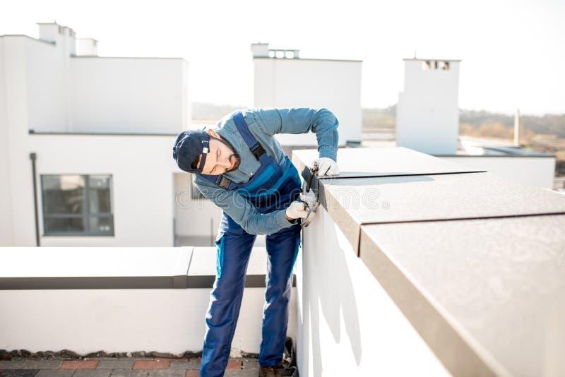 Byggmästare som monterar metallräkningen på balustraden av en nybygge fotografering för bildbyråer