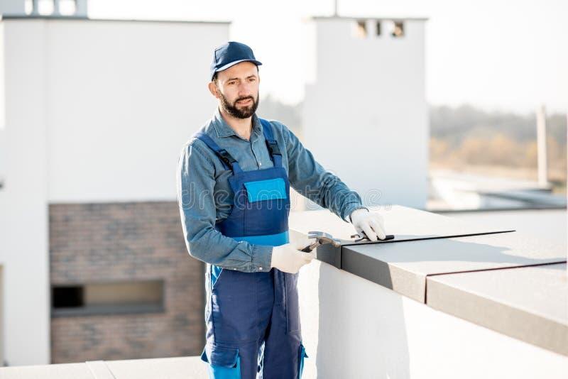 Byggmästare som monterar metallräkningen på balustraden av en nybygge royaltyfri foto