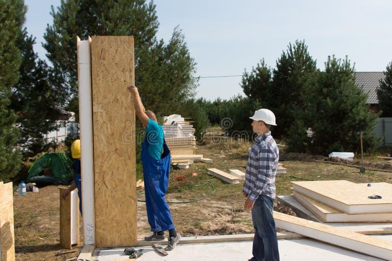 Byggmästare som reser upp isolerade väggpaneler royaltyfri foto