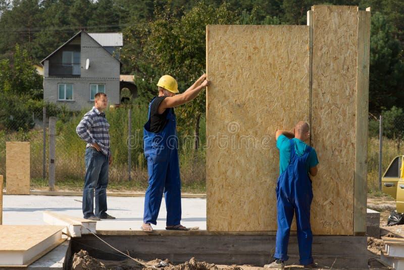 Byggmästare som reser upp väggpaneler arkivfoto