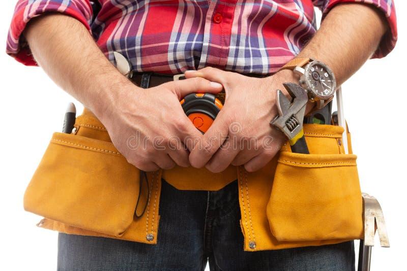 Byggmästare som rymmer att mäta bandet på bältenärbild arkivfoto