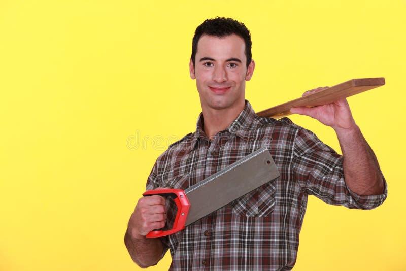 Byggmästare som rymmer en träplanka arkivfoto