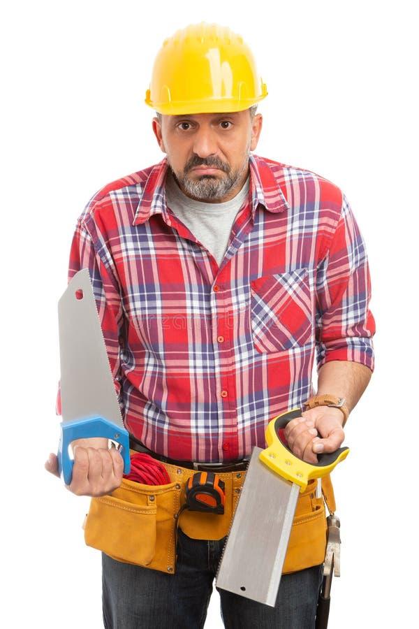 Byggmästare som rymmer sågar med förvirrat uttryck fotografering för bildbyråer