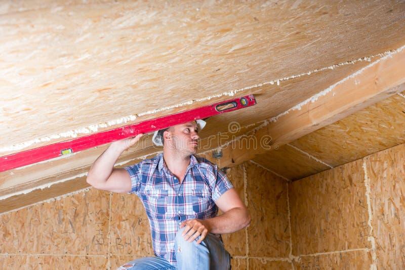 Byggmästare Using Level på tak i oavslutat hem arkivfoto