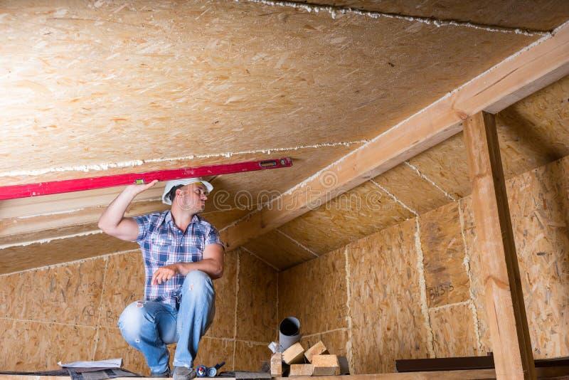 Byggmästare Using Level på tak i oavslutat hem royaltyfria bilder