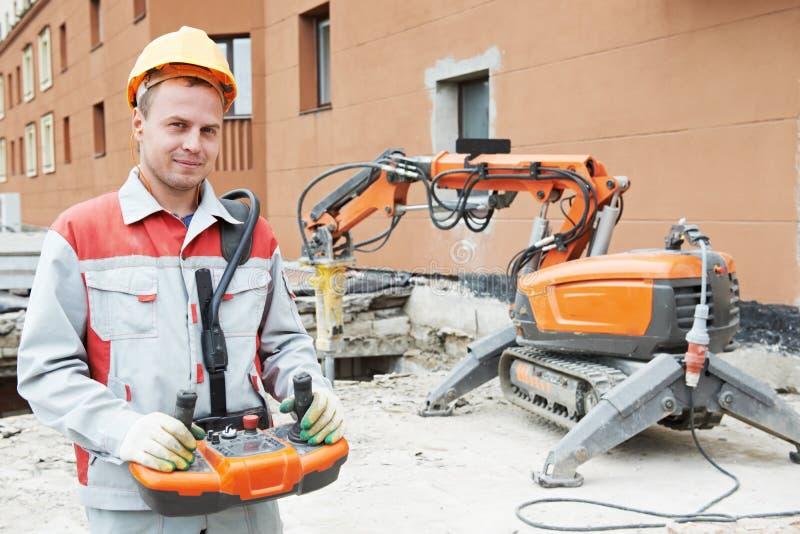 Byggmästarearbetarbearbetar med maskin fungerande rivning royaltyfri foto