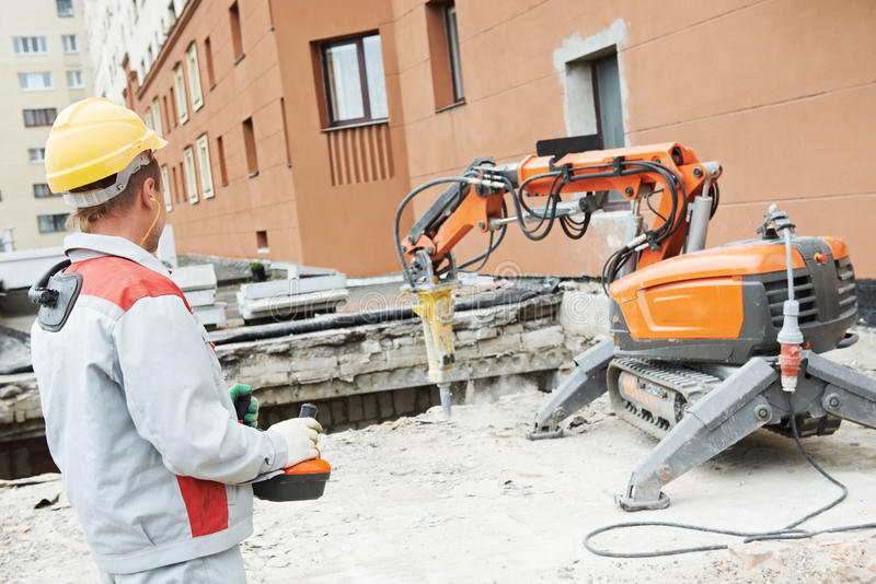 Byggmästarearbetarbearbetar med maskin fungerande rivning arkivfoto