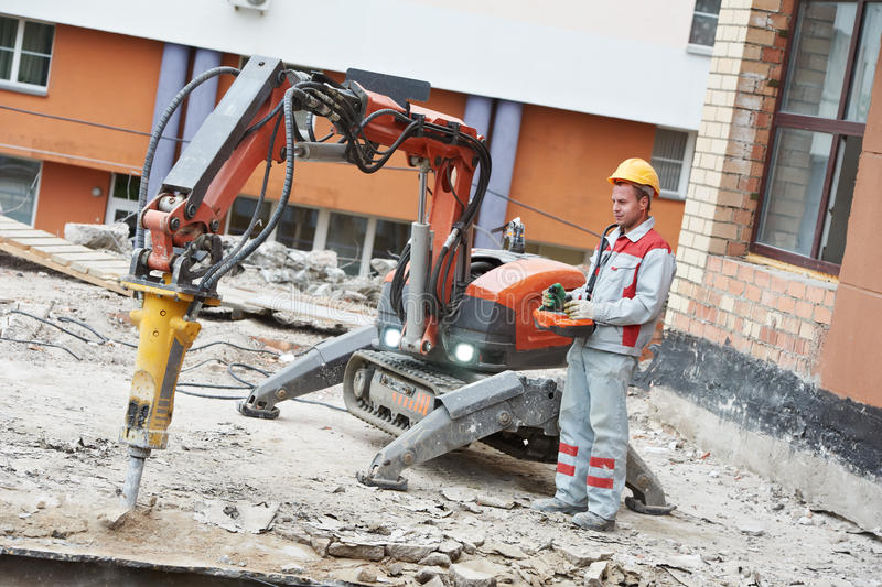 Byggmästarearbetarbearbetar med maskin fungerande rivning arkivbild