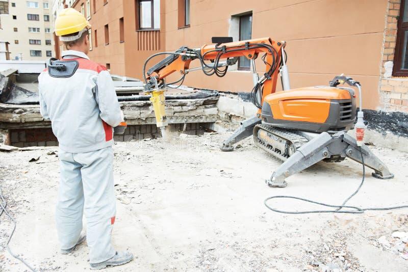 Byggmästarearbetarbearbetar med maskin fungerande rivning arkivfoton