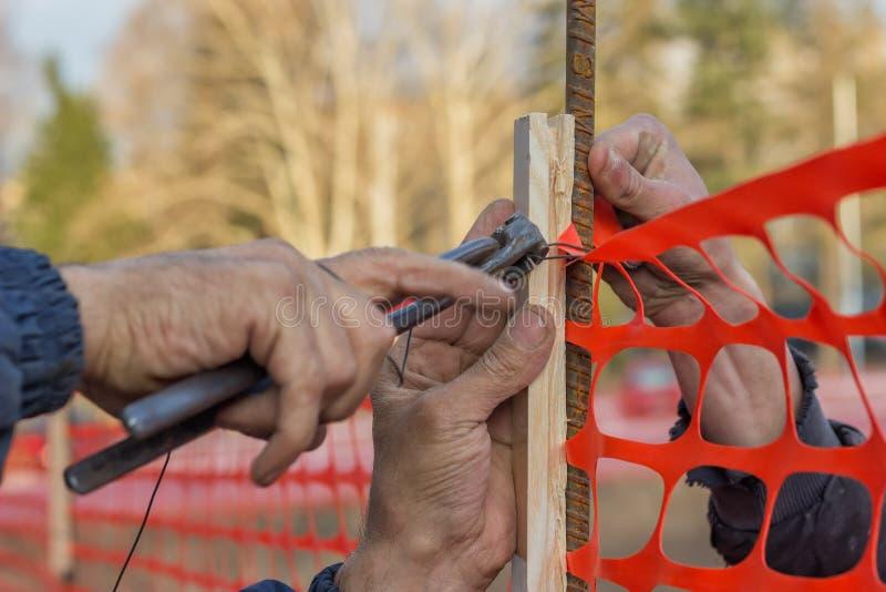 Byggmästarearbetare som installerar konstruktionssäkerhetsstaket 2 arkivfoton